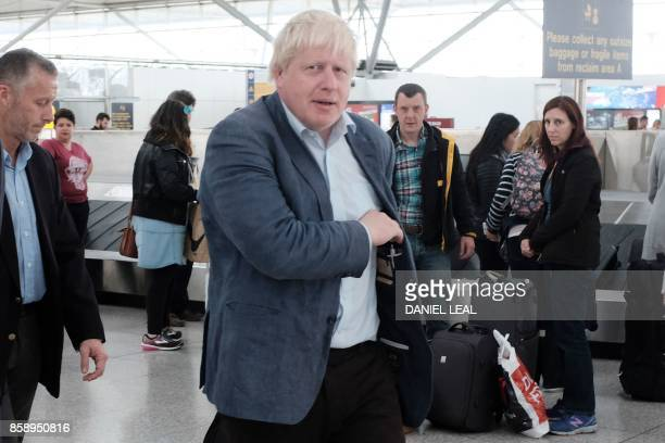 Britain's Foreign SecretaryBoris Johnson collects his baggage at London Stansted Airport airport north of London on October 8 2017 Newspaper reports...