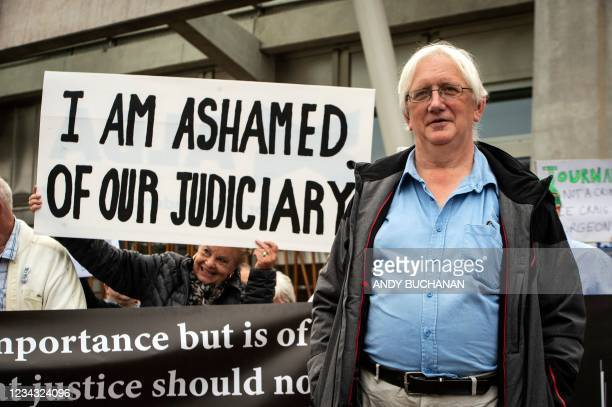 Britain's former ambassador to Uzbekistan, Craig Murray, poses with supporters outside the Scottish Parliament in Edinburgh on July 30, 2021 after...