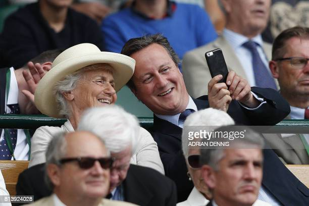 TOPSHOT Britain's former Prime Minister David Cameron sits with his mother Mary in the Royal Box on Centre Court following the women's singles...