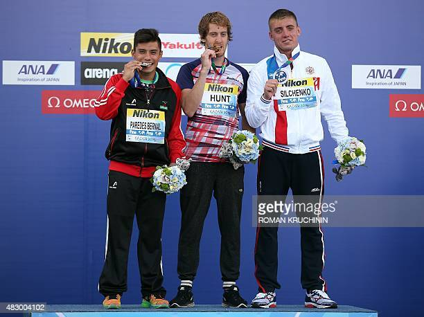 Britain's Gary Hunt poses on the podium with silver medalist Bernal Paredes of Mexico and Russian bronze medalist Artem Silchenko after winning the...