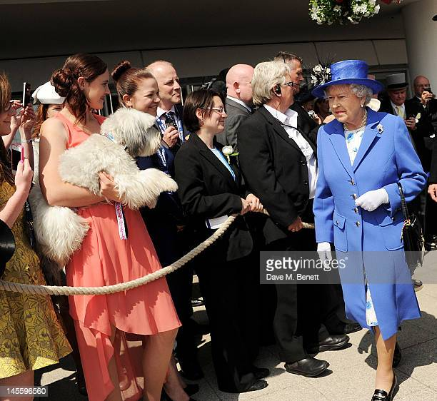 Britain's Got Talent winners Ashleigh Butler and dog Pudsey watch as Queen Elizabeth II walks by during Investec Derby Day at the Investec Derby...