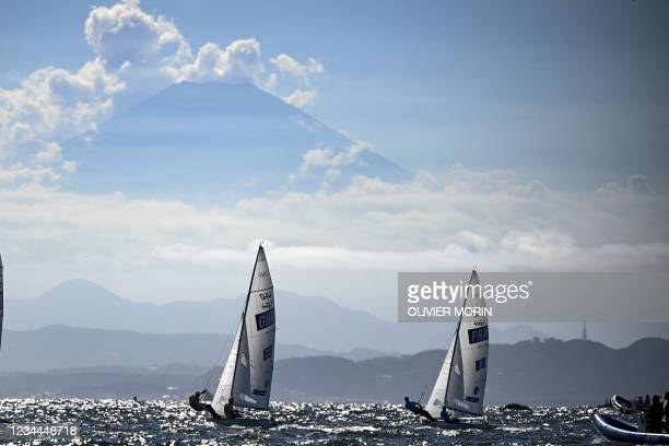 Britain's Hannah Mills and Eilidh Mcintyre and France's Aloise Retornaz and France's Camille Lecointre sail past Mount Fuji during the women's...