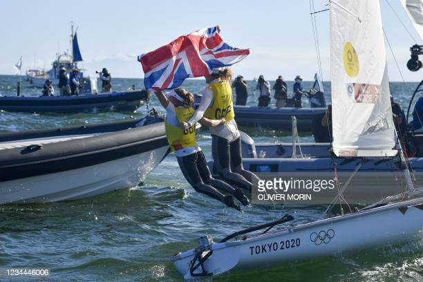 Britain's Hannah Mills and Eilidh Mcintyre celebrate after the women's two-person dinghy 470 medal race during the Tokyo 2020 Olympic Games sailing...