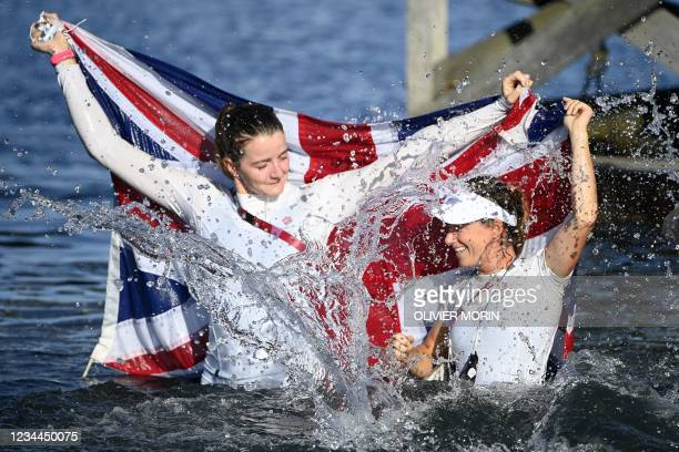 Britain's Hannah Mills and Eilidh Mcintyre celebrate in the water after the women's two-person dinghy 470 medal race during the Tokyo 2020 Olympic...