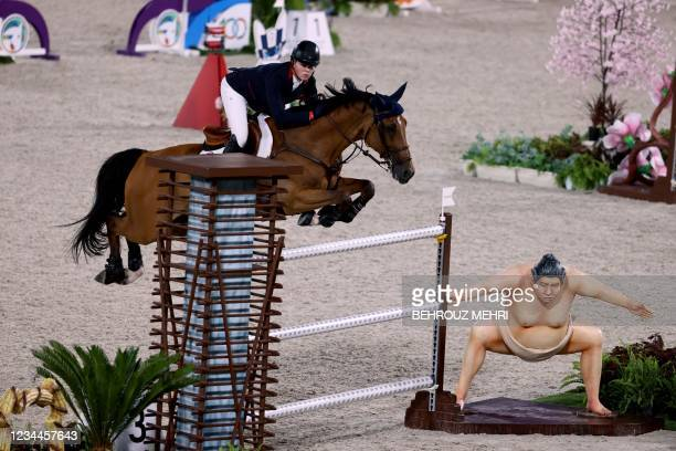 Britain's Harry Charles riding Romeo 88 jumps past a small sumo statue while competing in the equestrian's jumping individual finals during the Tokyo...