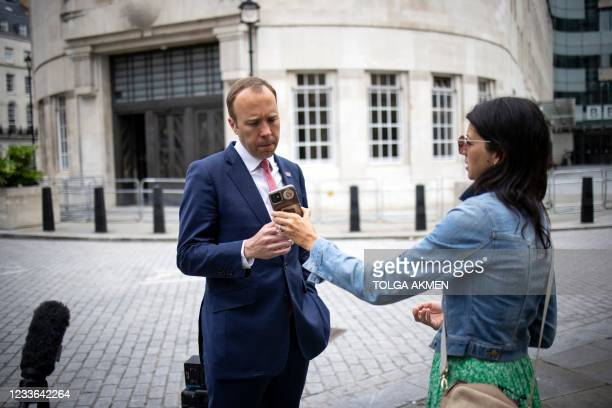 Britain's Health Secretary Matt Hancock , looks at the phone of his aide Gina Coladangelo as they leave the BBC in central London on June 6 after...
