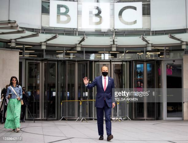 Britain's Health Secretary Matt Hancock , wearing a face covering due to Covid-19, walks with Gina Coladangelo as they leave the BBC in central...