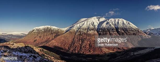 CONTENT] Britains highest mountain snow capped Ben Nevis in Autumn/Winter bathed in sunlight with autumnal colours on the lower slopes and a verdant...