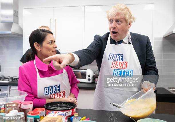 Britain's Home Secretary Priti Patel and Britain's Prime Minister Boris Johnson try their hands at baking during a visit to the HideOut Youth Zone on...