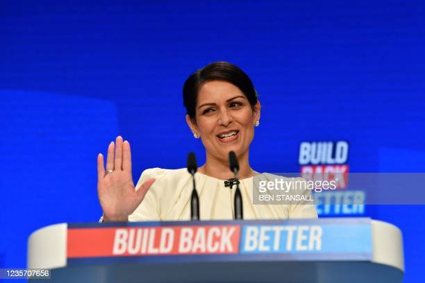 Britain's Home Secretary Priti Patel gestures as she speaks on the third day of the annual Conservative Party Conference at the Manchester Central...