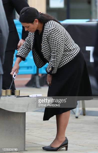 Britain's Home Secretary Priti Patel lights a candle during a vigil in memory of the three victims of the terror attack in Forbury Gardens, David...