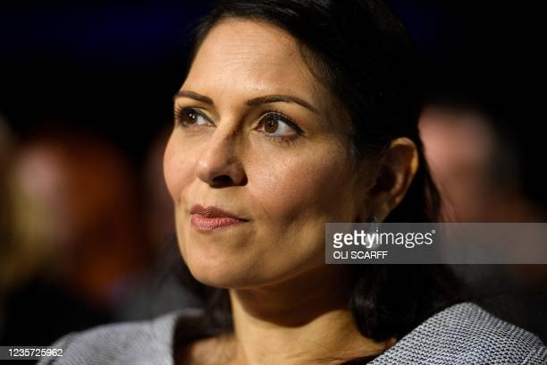 Britain's Home Secretary Priti Patel listens to the keynote speech of Britain's prime minister at the Manchester Central convention centre on the...