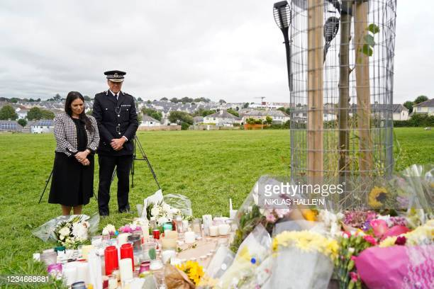 Britain's Home Secretary Priti Patel looks at floral tributesleft in memory of the victims of the August 12 shootings in Plymouth, in North Down...