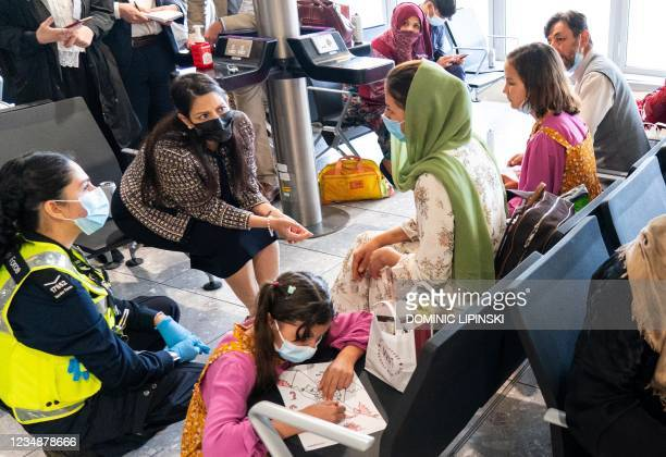 Britain's Home Secretary Priti Patel speaks to Afghan refugee Malalai Hussiny who arrived on an evacuation flight from Afghanistan, at Heathrow...