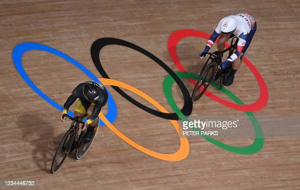Britain's Jason Kenny and Malaysia's Mohd Azizulhasni Awang compete in a heat of the men's track cycling sprint 1/32 finals during the Tokyo 2020...