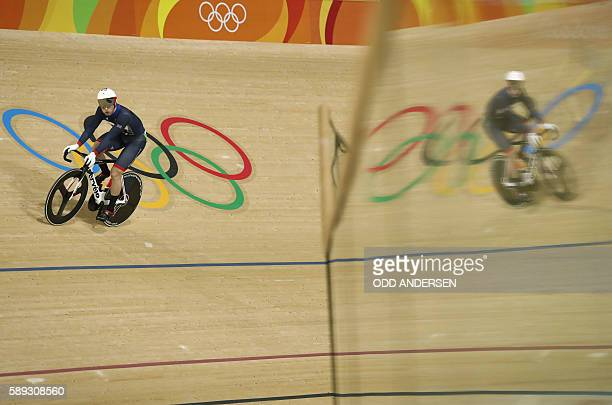 Britain's Jason Kenny is reflected in a glass barrier after competing in the men's Sprint quarter-finals track cycling event at the Velodrome during...