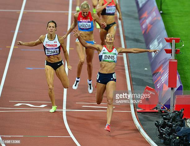 Britain's Jessica Ennis celebrates as she crosses the finish line of the women's heptathlon 800m heats at the athletics event of the London 2012...