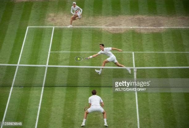 Britain's Joe Salisbury and Harriet Dart play against Britain's Neal Skupski during their mixed doubles final match on the thirteenth day of the 2021...