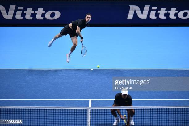 Britain's Joe Salisbury serves while playing with USA's Rajeev Ram against Poland's Lukas Kubot and Brazil's Marcelo Melo in their men's doubles...