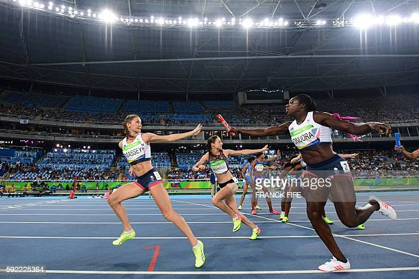 Britain's Kelly Massey grabs the baton from Britain's Anyika Onuora as they compete in the Women's 4x400m Relay Round 1 during the athletics event at...
