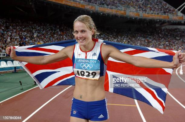 Britain's Kelly Sotherton celebrates with her country's flag after the women's heptathlon competitions at the Olympic Stadium 21 August 2004 during...
