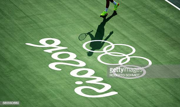 TOPSHOT Britain's Kyle Edmund casts a shadow over a Rio 2016 Olympic sign during a training session at the Olympic Tennis Center in Rio de Janeiro on...