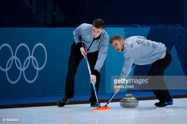 Britain's Kyle Waddell brushes with his teammate in front of the stone during the curling men's round robin session between Switzerland and Britain...