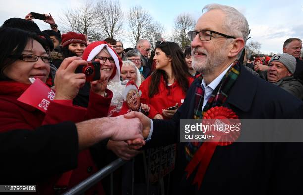 Britain's Labour Party leader Jeremy Corbyn greets supporters one holding a placard featuring an image of US President Donald Trump during a general...