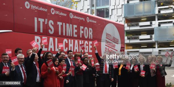 Britain's Labour Party leader Jeremy Corbyn holds up a copy of their general election manifesto with members of his shadow cabinet as he arrives for...