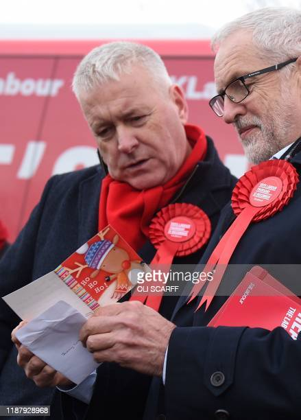 Britain's Labour Party leader Jeremy Corbyn reads a Christmas card as he attends a general election campaign event in Stainton Village near...