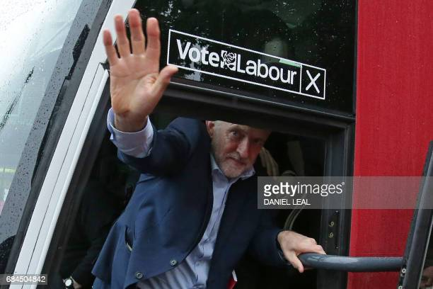 Britain's Labour Party leader Jeremy Corbyn waves to supporters as he climbs back onto the Labour battle bus in Southall west London on May 18 as...