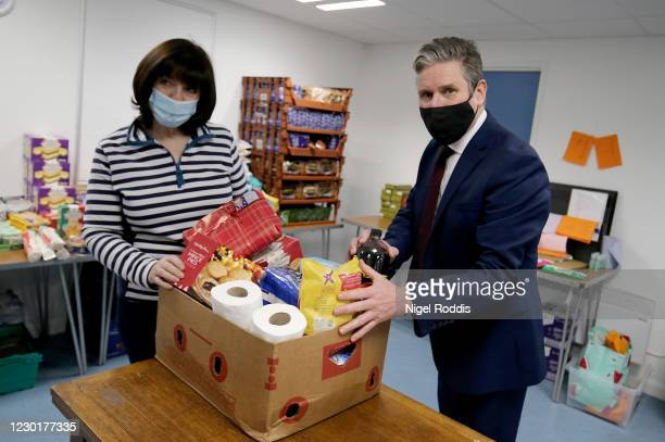 Britain's Labour Party Leader Keir Starmer packs food parcels with volunteers for residents during a visit to Lightwaves Leisure Centre on December...