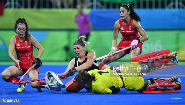 Britain's Laura Unsworth and New Zealand's Olivia Merry vie for the ball beside Britain's goalkeeper Maddie Hinch during the women's semifinal field...