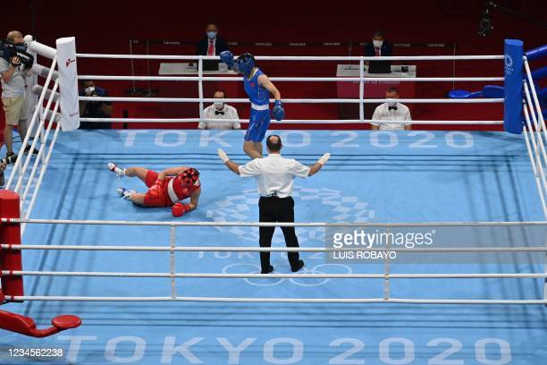 Britain's Lauren Price falls as she fights China's Li Qian during their women's middle boxing final bout during the Tokyo 2020 Olympic Games at the...