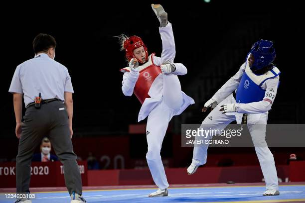 Britain's Lauren Williams celebrates with her coach winning against Ivory Coast's Ruth Gbagbi in the taekwondo women's -67kg semi-final bout during...