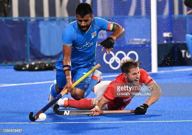 Britain's Liam Paul Ansell falls as he vies for the ball with India's Manpreet Singh during their men's quarter-final match of the Tokyo 2020 Olympic...