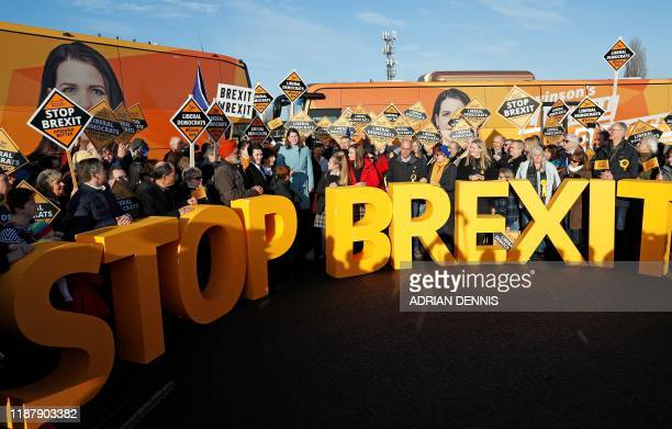 Britain's Liberal Democrat leader Jo Swinson stands between a Stop Brexit sign as she attends a general election campaign event at Esher Rugby Club...