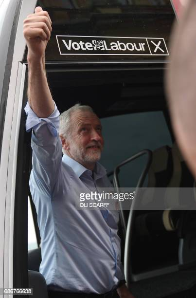 Britain's main opposition Labour Party leader Jeremy Corbyn acknowledges supporters as he boards his 'battle' bus after speaking during a general...