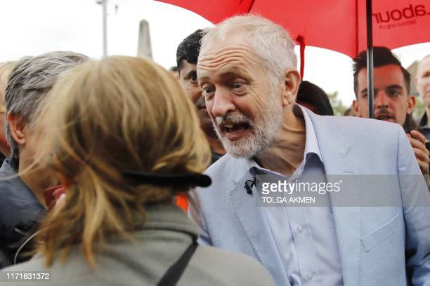 Britain's main opposition Labour Party leader Jeremy Corbyn chats to supporters at a gathering during a visit to Chingford in east London on...