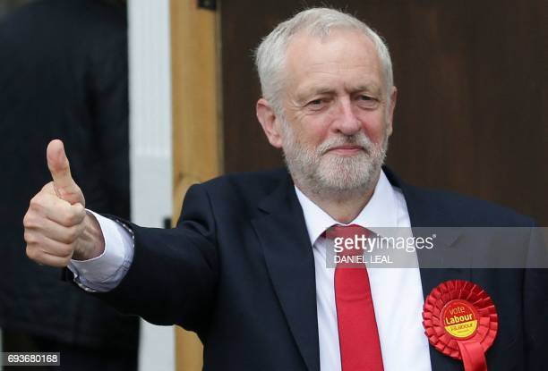 Britain's main opposition Labour Party leader Jeremy Corbyn gives a thumbs up as he arrives at a polling station to cast his vote in north London on...