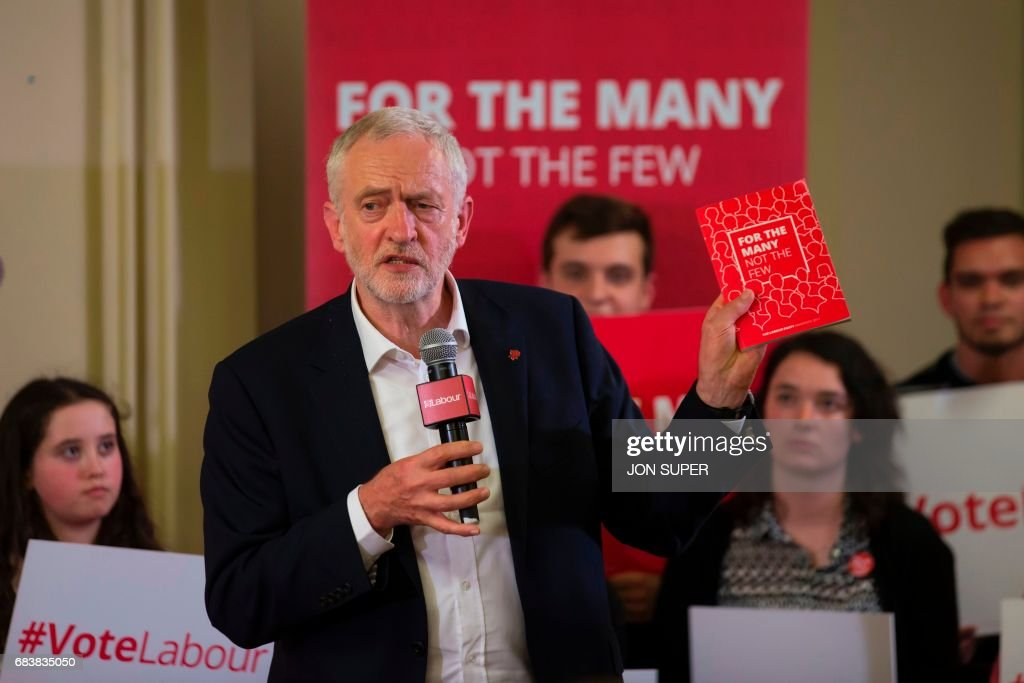 Britain's main opposition Labour Party leader Jeremy Corbyn holds up the party manifesto as he speaks at a general election rally at Swinnow Community Centre in Leeds, northern England on May 16, 2017. Britain goes to the polls to vote in a general election on June 8. /