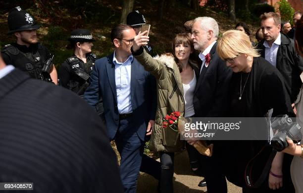 Britain's main opposition Labour Party leader Jeremy Corbyn poses for a 'selfie' photograph as he leaves after addressing supporters at a campaign...