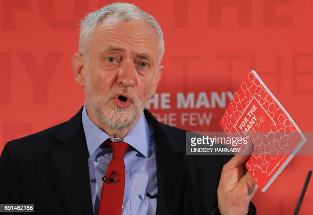 Britain's main opposition Labour Party leader Jeremy Corbyn speaks holding a copy of his party's manifesto during a general election event at the...