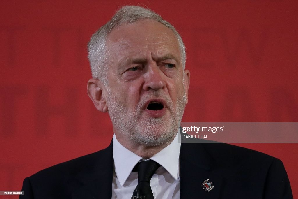 Britain's main opposition Labour party leader Jeremy Corbyn wears a 'Manchester' lapel pin as he makes a general election campaign speech in central London on May 26, 2017. Britain's politicians resume campaigning in earnest on Friday with national security thrust into the spotlight as police scramble to bust a Libya-linked jihadist network thought to be behind the Manchester terror attack. / AFP PHOTO / Daniel LEAL
