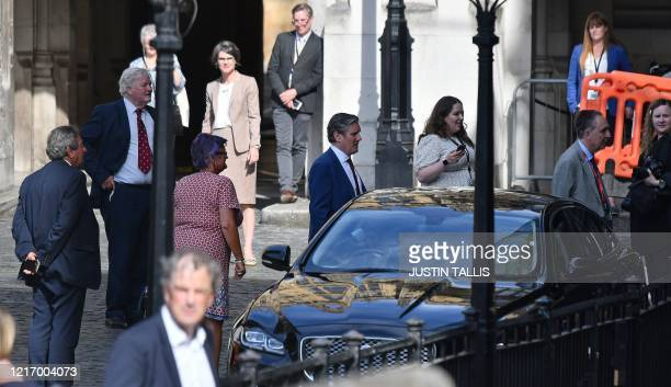 Britain's main opposition Labour Party leader Keir Starmer and other MPS are pictured queuing in a courtyard on the parliamentary estate to vote on...