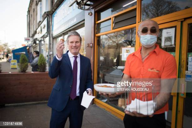Britain's main opposition Labour Party leader Keir Starmer meets with local shopkeepers and business owners during a walkabout in Kingsbury, north...