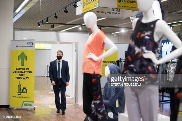 Britain's main opposition Labour Party leader Keir Starmer, wearing a face covering, walks past clothes displayed for sale during a visit to a...
