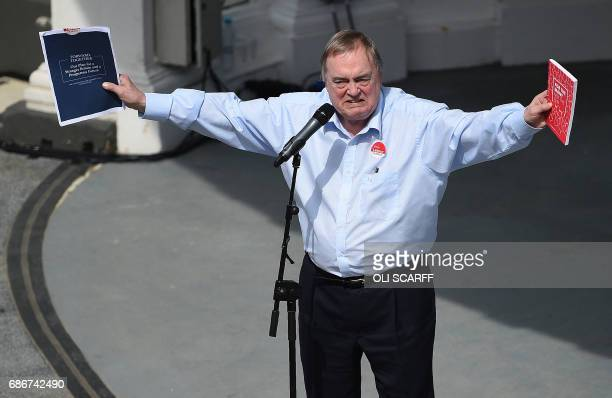 Britain's main opposition Labour Party's former deputy Prime Minister John Prescott holds up the ruling Conservative party's election manifesto and...