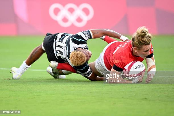 Britain's Megan Jones scores a try despite a tackle from Fiji's Alowesi Nakoci in the women's bronze medal rugby sevens match between Fiji and...