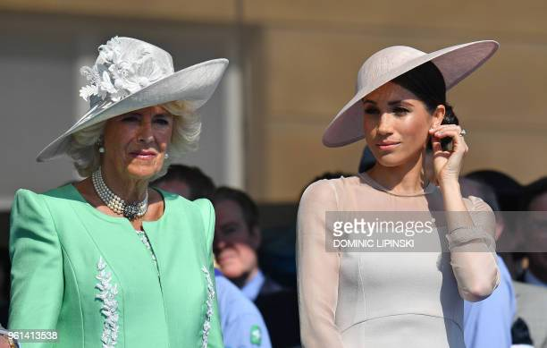 Britain's Meghan, Duchess of Sussex, and Britain's Camilla, Duchess of Cornwall attend the Prince of Wales's 70th Birthday Garden Party at Buckingham...